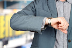 Businessman checking time on his watch at the airport. Royalty Free Stock Images