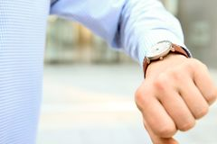 Businessman  checking time on his watch near with  office. Businessman  checking time on his watch near with  office Royalty Free Stock Photography