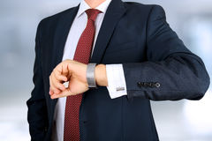 Businessman  checking time on his watch at office Royalty Free Stock Image