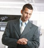 Businessman checking time in office. Smiling Stock Images