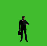 Businessman checking time over black background with copyspace. Royalty Free Stock Image