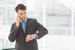 Businessman checking the time on the phone Royalty Free Stock Images