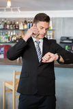 Businessman checking time while talking on the mobile phone Stock Images