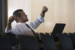 Businessman checking time on watch in empty conference room, stretching, laptop in lap, side view Stock Image