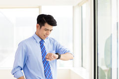 Businessman checking time from watch in office. Business man checking time from watch in office Stock Photo