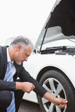 Businessman checking tire Royalty Free Stock Photography