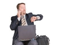 Businessman checking watch. Calling travelling businessman or salesman with laptop and luggage checks his watch afraid being too late for an appointment or a Royalty Free Stock Images