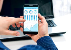 Businessman checks the financial analysis on smartphone. Phone interface has been created in a graphics program Royalty Free Stock Photo