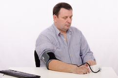 Businessman checks his blood pressure Royalty Free Stock Photos