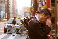 Businessman checks his mobile phone Stock Photo