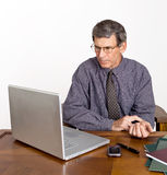 Businessman Checks His Pulse. Worried businessman at desk and computer checking his own pulse stock image