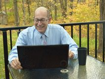 Businessman checks his Stock Portfolio Online. Businessman works at home outdoors with his laptop Stock Photos
