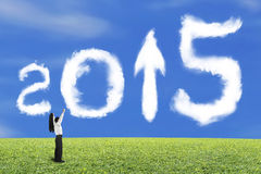 Businessman cheering 2015 arrow up shape clouds with sky grass. Businessman cheering for 2015 arrow up shape clouds with blue sky grass background Royalty Free Stock Photos