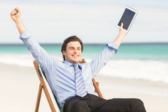 Businessman cheering on the beach Stock Photos