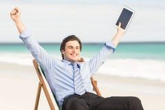 Businessman cheering on the beach Stock Photos