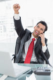Businessman cheering while on call at office desk Stock Image