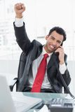 Businessman cheering while on call at office desk Royalty Free Stock Image