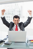 Businessman cheering in front of laptop at office desk Royalty Free Stock Images