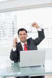 Businessman cheering in front of laptop at office desk Royalty Free Stock Photo