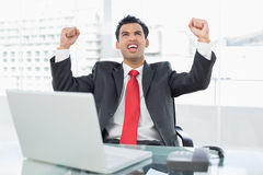 Businessman cheering in front of laptop at office desk Royalty Free Stock Photos