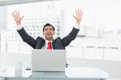 Businessman cheering in front of laptop at office desk Royalty Free Stock Photography