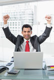 Businessman cheering in front of laptop at office Stock Images