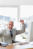Businessman cheering at his desk Royalty Free Stock Photos