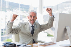 Businessman cheering in his office Stock Images