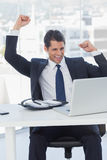 Businessman cheering and looking at his laptop Stock Images