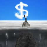Businessman cheering on mountain peak for dollar sign shape clou Royalty Free Stock Photos