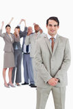 Businessman with cheering team behind him Stock Images