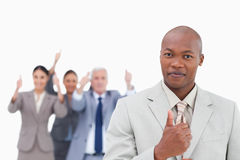 Businessman with cheering team behind him giving thumb up stock images