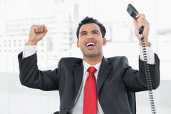 Businessman cheering with telephone receiver at office Royalty Free Stock Photography