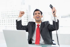 Businessman cheering with telephone receiver at office Stock Photography