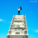 Businessman cheering on top of money stairs Stock Image