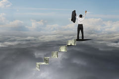 Businessman cheering on top of money stairs with natural cloudsc. Businessman cheering on top of money stairs with natural sky cloudscape background Royalty Free Stock Photography