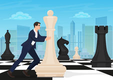 Businessman on the chess board. Man chess player moving figure on chessboard with the modern city background. Business Royalty Free Stock Photography