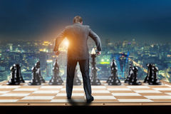 Businessman on the chess board. Ready to fight with black chess team Royalty Free Stock Photography