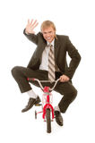 Businessman on children's bicycle Stock Images