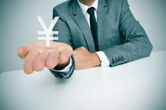 Businessman and chinese yuan or japanese yen sign. A businessman sitting in a desk showing a chinese yuan or japanese yen sign in his hand Stock Photos