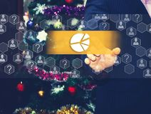 The businessman chooses chart, business diagram. On the touch screen, the backdrop of the Christmas tree and decorations. Special toning Royalty Free Stock Images