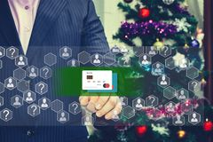 The businessman chooses the credit card on the touch screen. The backdrop of the Christmas tree and decorations. Special toning Stock Photography