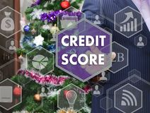 The businessman chooses CREDIT SCORE on the touch screen, the ba. Ckdrop of the Christmas tree and decorations. Special toning Royalty Free Stock Photo