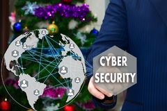 The businessman chooses CYBER SECURITY on the touch screen, the. Backdrop of the Christmas tree and decorations. Special toning Royalty Free Stock Images