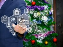 The businessman chooses EMAIL MARKETING on the touch screen, the. Backdrop of the Christmas tree and decorations. Special toning Royalty Free Stock Image
