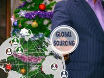 The businessman chooses GLOBAL SOURCING on the touch screen, the. Backdrop of the Christmas tree and decorations. Special toning Royalty Free Stock Photos