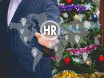 The businessman chooses HR,human resources  on the touch screen. The businessman chooses HR,  human resources  on the touch screen, the backdrop of the Christmas Stock Image