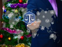 The businessman chooses LIBRA  on the touch screen. The backdrop of the Christmas tree and decorations. Special toning . Business, security, Internet, court Royalty Free Stock Photography