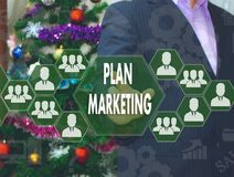 The businessman chooses MARKETING PLAN  on the touch screen. The backdrop of the Christmas tree and decorations. Special toning Stock Images
