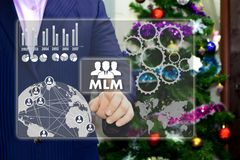 The businessman chooses MLM, multi-level marketing on the touch. Screen, the backdrop of the Christmas tree and decorations. Special toning Stock Photos